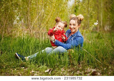 Family Time. The Mother Sits On The Lawn, And Her Little Daughter Is Sitting On Her Lap. They Are Ta