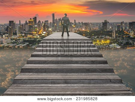 Businessman Climbed On Top Of The Stairs Which Can See Top View Of Cityscape Over The Clouds Backgro