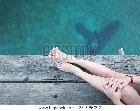 Close Up Beauty Woman Leg And Bare Feet Sitting On Wooden Floor Over Blue Sea For Relaxation. Vacati