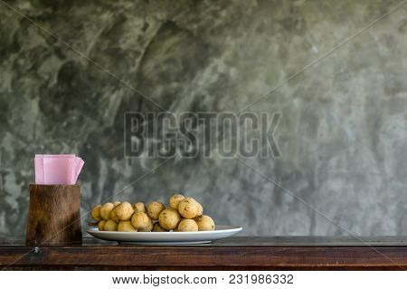 Wollongong In The Plate With Tissues Paper On The Wood Table With Brick Wall Background