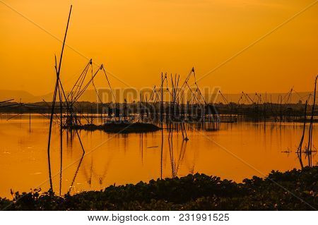 Traditional Bamboo And Wooden Fishing Tools Installed In Rural Swamp For Fishing During Sunset.