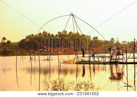 Unidentified Fisherman On Bamboo Scaffolding Fishing By Using Traditional Bamboo Fishing Tools In Sw