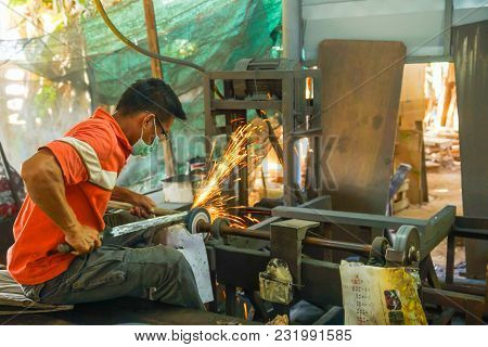 Lampang, Thailand - November 2, 2012: Sword Maker Grinding Sword With Grinding Electrical Machine In