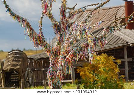 A Tree Of Desires With Colorful Ribbons In Front Of An Old Wooden Watchtower.