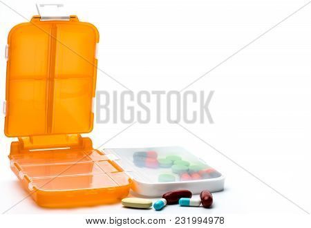 Orange Pills Box With Tablets And Capsule Pills Isolated On White Background With Copy Space. Prepar