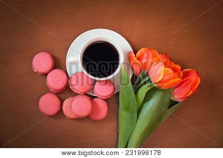 Cup Of Coffee With Pink Macaroons And Tulip Flowers On Wooden Background. Top View.