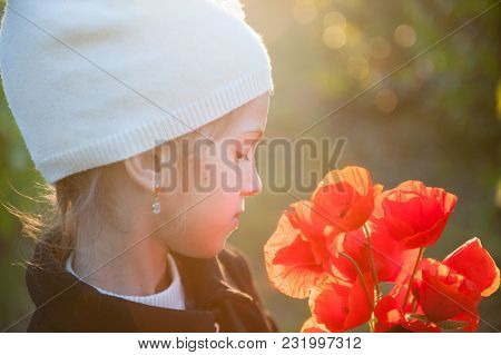 Dreamy Little Girl In White Woolen Hat With Bouquet Of Orange Poppy Flowers Backlit With Spring Suns
