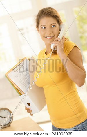Happy young woman working from home. Woman talking on phone in home office, working.
