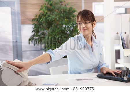 Attractive young female office worker is busy working in office, using laptop computer, reaching for landline phone, smiling.