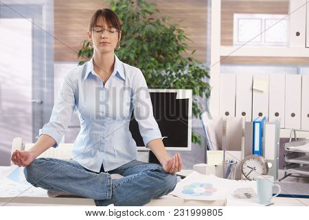Young female office worker sitting in lotus position on top of desk at office, meditating, eyes closed.