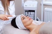 The cosmetologist makes the procedure Microcurrent therapy of the facial skin of a beautiful, young woman in a beauty salon.Cosmetology and professional skin care. poster