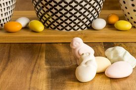Easter Candy Eggs And Animal Shaped Marshmallows On Wooden Surface Besides Withe Bowls With Black Pa