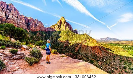 Woman Hiking At Sunrise On The Watchman Trail In Zion National Park In Utah, Usa. The Early Morning