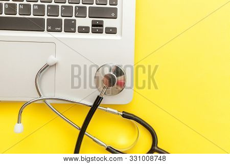 Stethoscope Keyboard Laptop Computer Isolated On Yellow Background. Modern Medical Information Techn