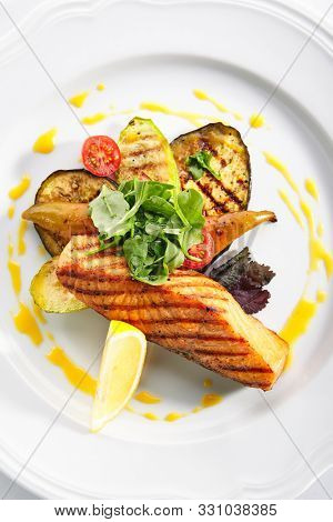 Top View of grilled salmon steak with bbq vegetables, fresh greens and spices. Barbecue red trout fish fillet decorated with spicy greens on white restaurant plate isolated topview