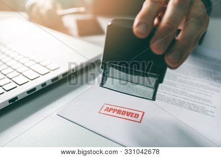 Approved Stamp - Businessman Stamping Document In Office