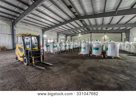 Large Industrial Warehouse Of Chemicals. Large White Bags Filled With Powder Are Arranged In Long Ro