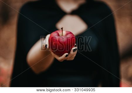 Woman As Witch In Black Offers Red Apple As Symbol Of Temptation, Poison. Fairy Tale Concept, Hallow
