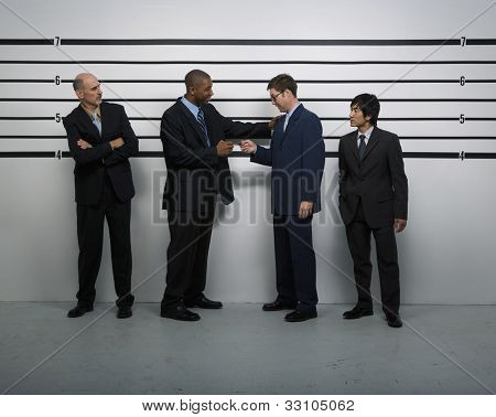Multi-ethnic businessmen in police line up
