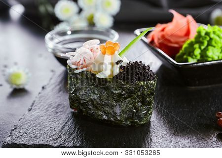 Gunkan with crab meat and masago caviar. Asian cuisine restaurant dish, menu item. Traditional oriental food, national japanese cooking. Delicious sushi, seafood on wooden platter closeup