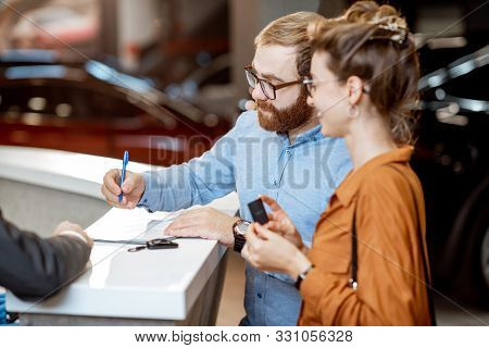 Young Couple Signing Some Documents, Buying A New Car In The Modern Showroom Of The Car Dealership