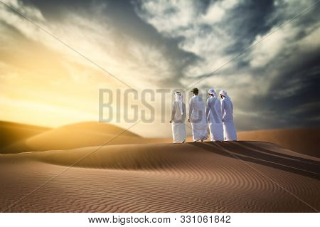 Four Proud Arab Young Man Standing On The Dune In Desert Celebrating  Spirit Of The Union - Uae Nati