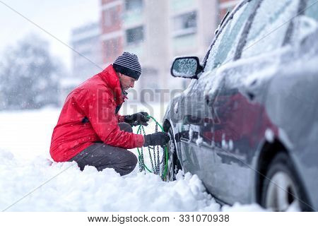 Young Man Putting Winter Chains On Car.confused Man Does Not Know How To Put Snow Chains On Car Tire