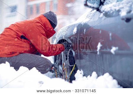 Snow Chains On The Wheels Of Car.man Preparing Car For Travelling At Winter Snowy Day.
