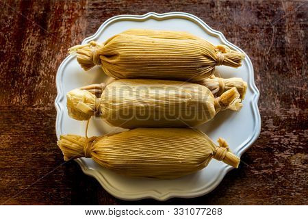 Unwrapped Stacked Mexican Tamales In White Plate On Grunge Wooden Table Viewed From Above - Ethnic F