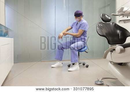 Hand pain in the dental practice.Caucasian dentist in uniform, sitting on mobile dental saddle  having short break for regeneration after long working hours in his office