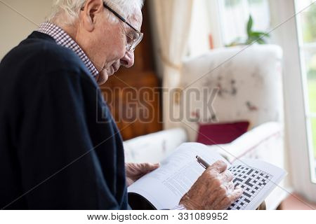 Senior Man Doing Crossword Puzzle At Home