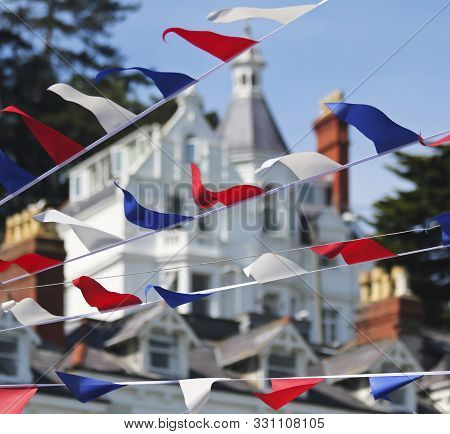 A Bunting Of Red, White And Blue Fourth Of July Flags, Victorian Architecture Behind, Main Street, A
