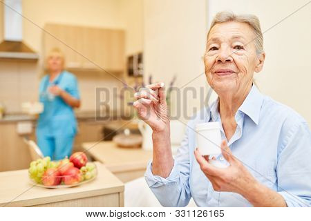 Senior woman takes medication in supervised senior citizen home with caregiver
