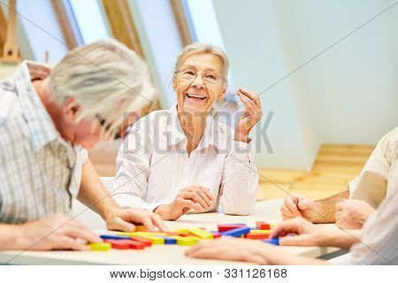 Senior group has fun playing with building blocks in retirement home or at home