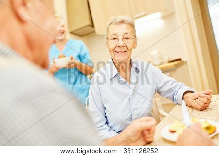 Seniors at the kitchen table in assisted living with nursing assistant in the background
