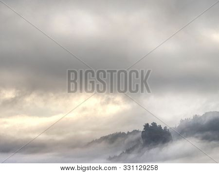 Cloudy Hilly Landscape. View Over Heavy Cloud Into Rocky Gulch Full With Deep Forest. Sun Hidden In