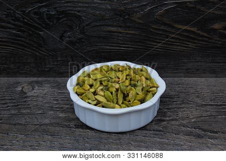 Green Cardamon Seeds In A White Dish With A Rustic Background