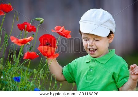 Cute little boy smells a flower