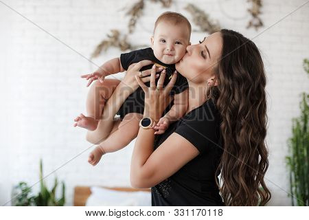 Mother And Child On A White Bed.mom And Baby Boy In Shorts Playing In Sunny Bedroom. Parent And Litt