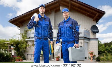 Portrait Of Smiling Two Young Male Electrician Standing In Front Of House With Electrician Kits