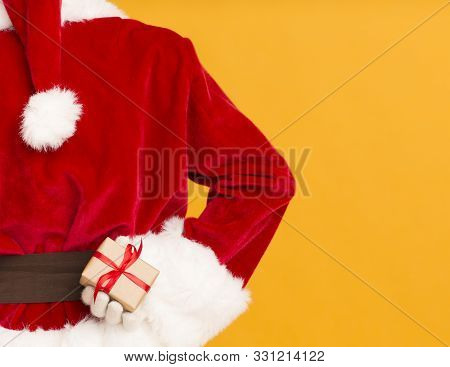 Christmas Surprise. Crafty Santa Hiding Present In Hand On Orange Background, View From Back, Copy S