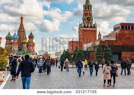 Moscow, Russia - October 08, 2019: Tourists Walking Along Red Square In Moscow Against Historical Bu