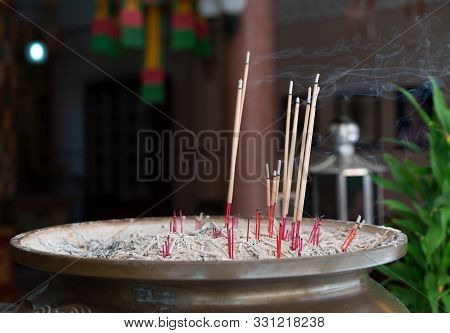 Incense Stick Burning In A Metal Pot At Religious Thai Buddhist Temple - Multiple Joss Sticks Burnin
