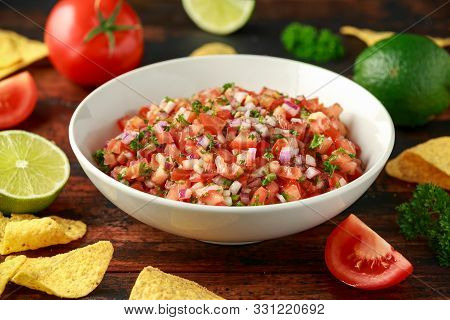 Mexican Tomato Salsa In White Bowl With Lime, Red Onion, Jalapeno Pepper, Parsley And Tortilla Chips