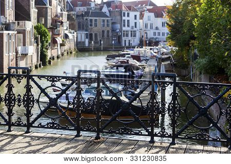 Nostalgia view through a cast iron bridge railing on a harbor and buildings in Dordrecht with selective focus on the railing poster