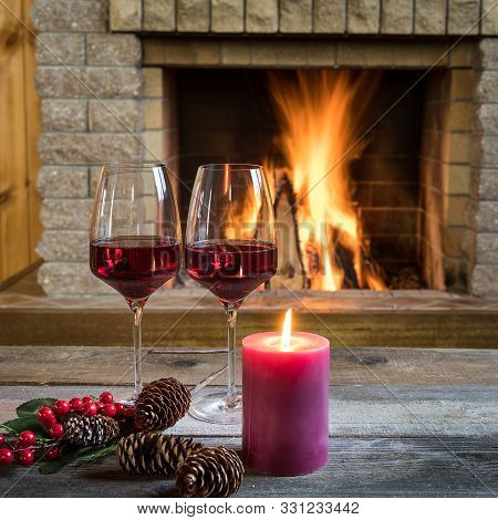 Christmas Eve. Two Glasses Of Red Wine Candle And Christmas Decorations Near Cozy Fireplace, In Coun