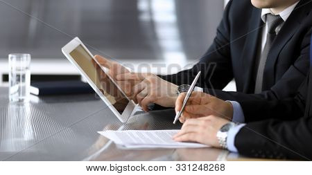 Businessman Using Tablet Computer And Work Together With His Colleague Or Partner At The Glass Desk