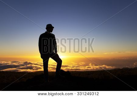 Man Leader Stands On A Mountain At Sunset High Above Clouds. Success And Conquest Of Peaks, Aspirati