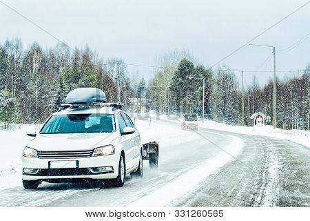Car With Roof Luggage Rack In Road In Finland