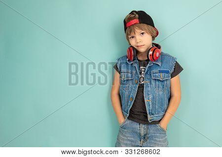 A Cool Tenager Boy In Denim Jaket And Shorts, Red Earphones, Black Cap, Stands In Front Of The Camer